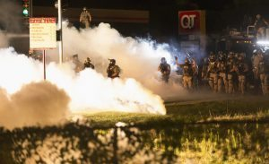 Riot police clear a street with smoke bombs while clashing with demonstrators in Ferguson, Missouri August 13, 2014. Police in Ferguson fired several rounds of tear gas to disperse protesters late on Wednesday, on the fourth night of demonstrations over the fatal shooting last weekend of an unarmed black teenager Michael Brown, 18, by a police officer on Saturday after what police said was a struggle with a gun in a police car. A witness in the case told local media that Brown had raised his arms to police to show that he was unarmed before being killed. REUTERS/Mario Anzuoni (UNITED STATES - Tags: CRIME LAW CIVIL UNREST TPX IMAGES OF THE DAY) - RTR42CPJ